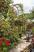 Torbogen aus Metall als Rankhilfe in sommerliche, ländlichem Garten mit Natursteinmauer