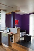 Counter with base cabinets adjoining platform in open-plan interior with purple-painted wall