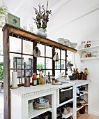 White kitchen counter against partition with lattice windows in simple wooden house