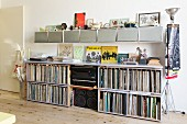 Record collection and hi-fi in open-fronted sideboard below row of wall-mounted cabinets