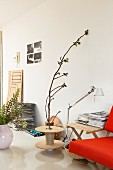 Wooden reel used as side table, branch, designer standard lamp and red sofa