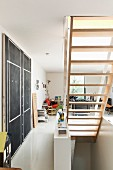 Underside of staircase next to black panel on wall in open-plan interior
