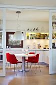 Blick auf weißen runden Tisch mit roten Designerstühlen in weißer Einbauküche mit gelb beleuchteten Hängeschränken