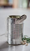 Tin can, tin opener and ribbon and beads for decoration