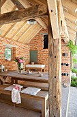 Roofed, rustic terrace in renovated farm building with exposed brickwork