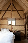 Restored, half-timbered wall with gable-end window in vintage-style bedroom