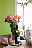 Brennende Kerze in Flasche vor Pfingstrosenstrauss auf Tablett, daneben Kaffeekanne mit Blumenmuster