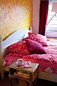 Rote Bettwäsche mit floralem Muster auf Doppelbett mit weißem Kopfteil, vor tapezierter Wand mit Blumenmuster