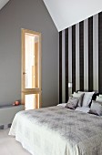 Double bed against black and grey striped wallpaper in minimalist attic bedroom
