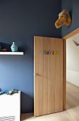 Boy's bedroom with pale, wooden, open interior door and fake plush animal head on blue wall