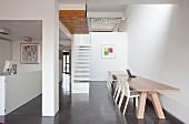 weiße Stühle an Holztisch in modernem Wohnraum im Hintergrund minimalistische Treppe und Galerie