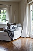 Gemütlicher Polsterstuhl mit Kissen und Hocker im Wohnzimmer