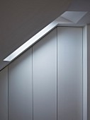 Simple fitted wardrobes without handles under sloping ceiling with skylight