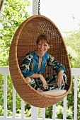 Woman in wicker hanging chair (classic Scandinavian design by Nanna Ditzel) on white veranda