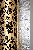 Sconce lamp with floral, printed lampshade mounted on wall with structured silver surface
