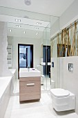 Modern bathroom with mirrored niche behind washstand and mirror behind bamboo canes above toilet