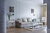 Elegantes Sofa und weisse antikisierende Möbel vor lichtgrauer Wand mit Stuckrahmen und Leuchter-Kassetten