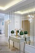 Elegant dekorierte Stilkommode, flankiert von verzierten Leuchten vor einer Spiegelwand