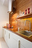 Kitchen counter with white base unit, exotic wood worksurfaces and back wall, cylindrical extractor hood with LED lights