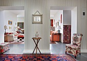 Continuous, open-plan interior belonging to collector: mixture of patterns and styles with Oriental rugs, colourful textiles and grey and white striped wallpaper