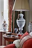 Leuchte mit kelchartigem Glasfuss auf antikem Beistelltisch, Deckelvase aus Porzellan und klassisch traditioneller Vorhang am Fenster