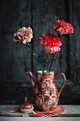 Three carnations in retro-style, painted china coffee pot on doily against dark background