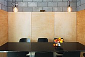 Fruit dish on black dining table in niche with wooden wall panels on concrete block walls