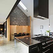 Stainless steel kitchen counter under extractor hood, dining area in wood-panelled niche and concrete block wall in modern, open-plan interior