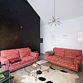 Sofa set with dusky pink brocade upholstery and delicate, curved metal coffee table on animal-skin rug in modern interior with black stucco lustro wall in background