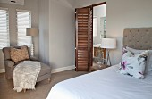 Double bed with taupe headboard and matching armchair in bedroom