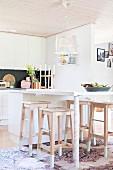 White modern breakfast bar and wooden bar stools in open-plan kitchen