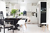 Dining area with black-painted table and classic shell chairs in open-plan fitted kitchen