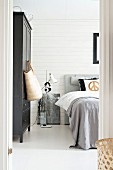 View through open door into bedroom; black-painted wardrobes to ones side and standard lamp next to bed with grey bedspread
