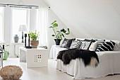Tierfell und viele Kissen auf Sofa mit weißem Überwurf und Couchtisch in Loungebereich in ausgebautem Dach
