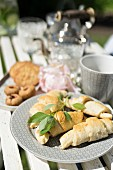 Home-made croissants and basil on garden table