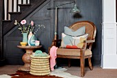 Antique armchair with scatter cushions next to seagrass stool and round stone table