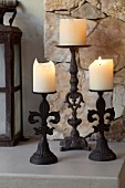 Lit pillar candles on three wrought iron candle sticks