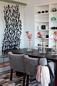 Row of vases holding protea flowers on dark wooden dining table with light grey upholstered chairs