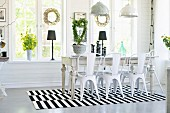 Retro metal chairs around rustic dining table on black and white striped rug below pendant lamps in dining room with wreaths on windows