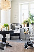 Black, round table and rattan chair next to retro serving trolley below lattice window; retro-style ride-on toy car to one side