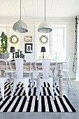 Retro metal chairs at rustic dining table on black and white striped rug below pendant lamps with metal lampshades