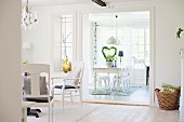 White-painted armchairs in front of wide, open doorway leading to dining room