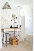Console table with peeling paint against staircase with white wooden balustrade in hallway