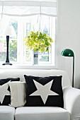 Kissen mit weißem Stern auf schwarzem Grund auf weißem Polstersofa vor Fenster, seitlich Stehleuchte