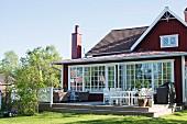 Erhöhte Holzterrasse vor Anbau mit weissen Sprossenfenstern und rotbraun gestrichenem Holzhaus