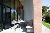 Sonnenbeschienene, möblierte Terrasse mit gebogener Beton Bank an Wand, gegenüber verglaste Fassade zeitgenössischer Architektur