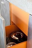 Kitchen drawer with orange interior holding stainless steel saucepans