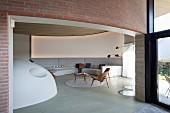 Extravagante Lounge mit gebogener Wand, davor eingebaute Sofalandschaft in Hellgrau, seitlich massgefertigter Ofen als Halbkugel