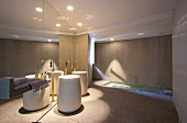 Cylindrical pedestal sink with brass floor-mounted taps against mirrored wall in luxurious bathroom with sunken bathtub