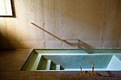 Sunken concrete bathtub with brass taps and minimalist handrail on concrete wall
